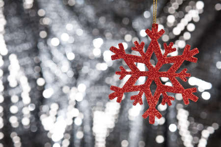 Red snow flake on a silver glitter background for Christmas photo