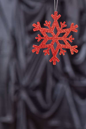 Red snow flake on a black background for Christmas photo