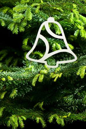 Bell shape Christmas ornament in fresh green Christmas tree photo