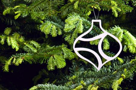 Bauble shape Christmas ornament in fresh green Christmas tree photo