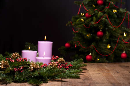 Three candles in an advent flower arrangement for advent and Christmas, with a christmas tree photo