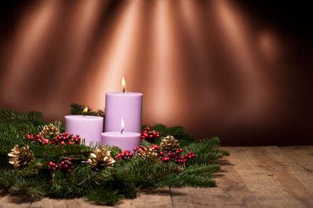 velas de navidad: Tres velas en un arreglo de flores advenimiento de Adviento y Navidad en una superficie de madera Foto de archivo