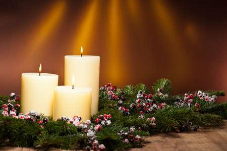 advent: Drie kaarsen in een komst bloemstuk voor Advent en Kerstmis op een houten oppervlak