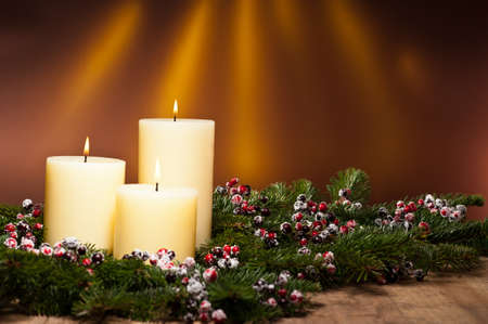 advent advent: Three candles in an advent flower arrangement for advent and Christmas on a wooden surface