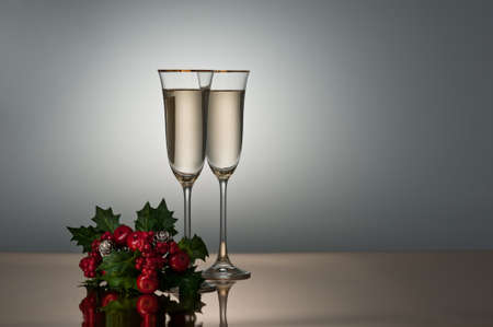 champagne flutes: Two champagne glasses on a golden surface decorated with holly