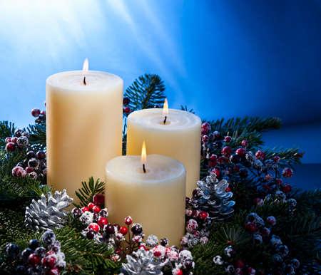 velas de navidad: Tres velas en un arreglo de flores advenimiento de Adviento y Navidad Foto de archivo
