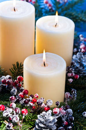 Three candles in an advent flower arrangement for advent and Christmas Stock Photo - 14201921