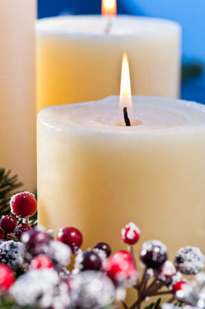 Three candles in front of an blue background, an advent flower arrangement for advent and Christmas Stock Photo - 14219322