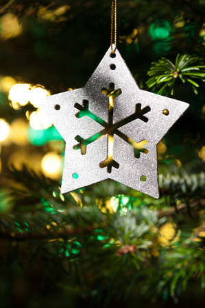 Decorative Silver Star ornament in a Christmas tree infront of a glitter background Stock Photo - 14201925