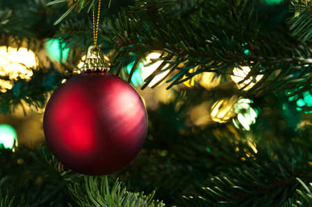 Decorative red bauble in a Christmas tree in front of a glitter background Stock Photo - 14219324