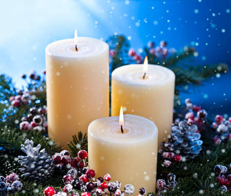 Three candles in an advent flower arrangement for advent and Christmas with snow fall
