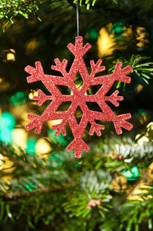 Red artificial snow flake in a christmas tree in front of a reflecting color background photo