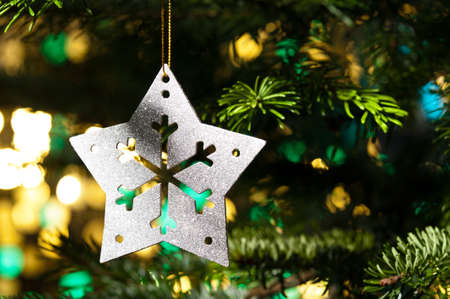 Decorative Silver Star ornament in a Christmas tree infront of a glitter background Stock Photo - 14265114