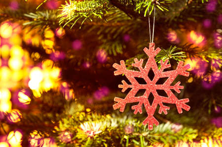 Red snow flake in a christmas tree with neon colors and nice glow photo