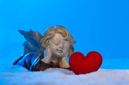 angels in heaven: Angel in a beautiful blue snow setting, shows heart