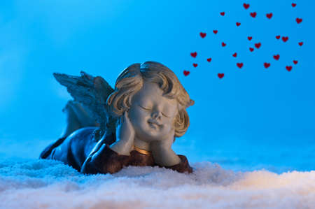 Angel in a beautiful blue snow setting, shows heart photo