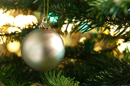 Decorative gold bauble in a Christmas tree in front of a glitter background Stock Photo - 14463238