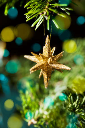 Decorative Gold Star ornament in a Christmas tree infront of a glitter background Stock Photo - 14463231