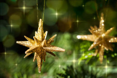 Decorative Gold Star ornament in a Christmas tree infront of a glitter background