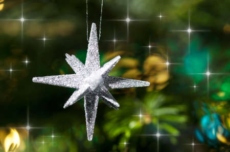 Decorative silver Star ornament in a Christmas tree infront of a glitter background photo