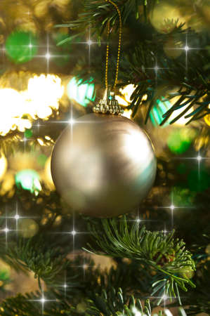 Decorative gold bauble in a Christmas tree in front of a glitter background Stock Photo - 14463229