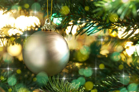 Decorative gold bauble in a Christmas tree in front of a glitter background Stock Photo - 14463242