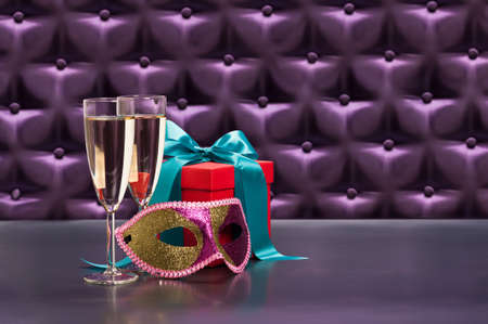 New Years celebration items in front of a button tufted purple silk background photo