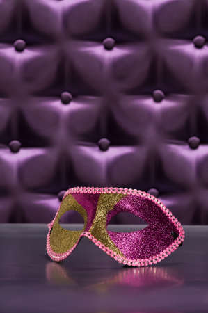 tufted: Elegant mask for Masquerade in front of a button tufted purple silk background