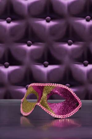 Elegante Maske für Masquerade vor einem Knopf getuftet lila Seide Hintergrund