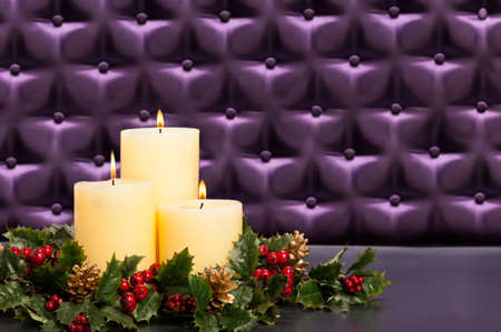 button tufted: Advent flower arrangement with burning candles in front of a button tufted purple silk background