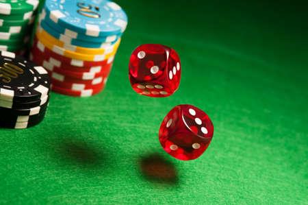 Rolling červené kostky na kasino stůl s čipy