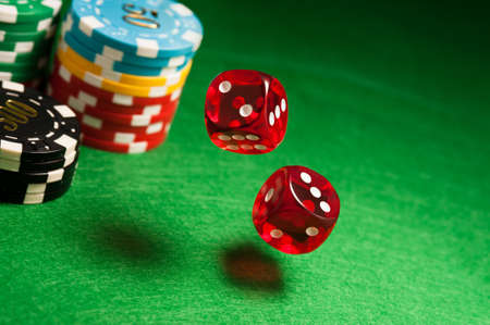 casino tokens: Rolling red dice on a casino table with chips Stock Photo