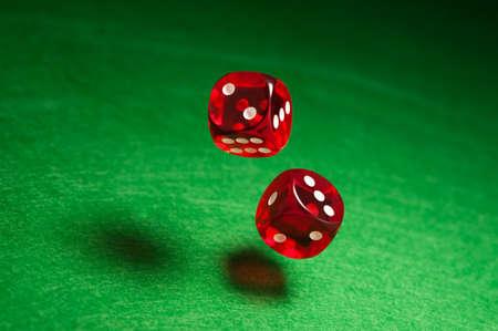 Rolling červené kostky nad zeleném povrchu Reklamní fotografie