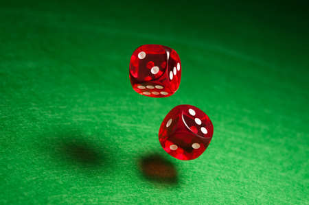 red dice: Rolling red dice over green surface