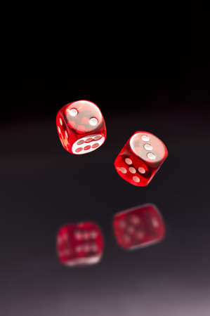 dice: Rolling red dice over black grey background