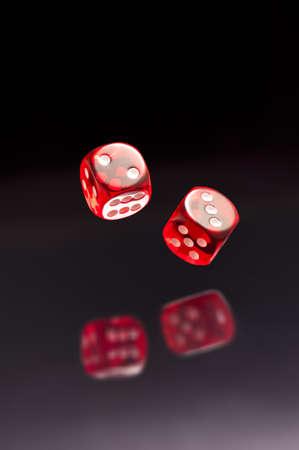 Rolling rode dobbelstenen op een zwarte grijze achtergrond Stockfoto