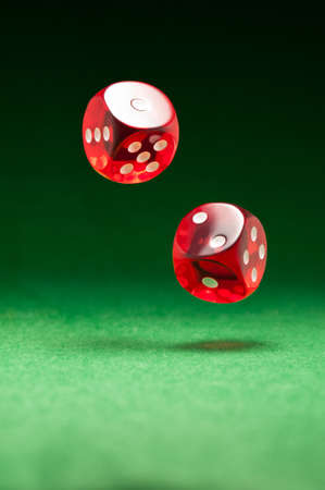 Rolling red dice over green surface photo