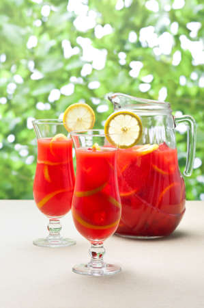 carafe: Chilled Orange Lemon Sangria in a summer setting
