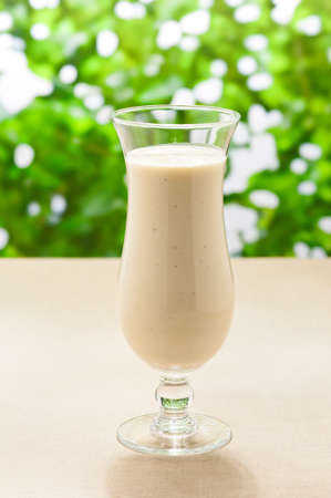 Banana milk shake with real fruit and a green background photo