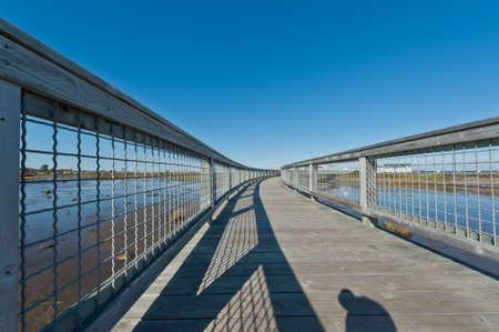 elevated walkway: Elevated walkway above a salt marsh during a sunny day Stock Photo