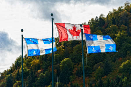 canadian icon: Canadian and the Quebec flag in autumn setting on a cloudy day