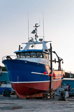 Fish trawler on land during off peak season, ship goes through maintenance Stock Photo - 16867631