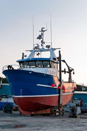 Fish trawler on land during off peak season, ship goes through maintenance Stock Photo - 16867631