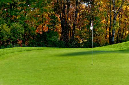 Golfové hřiště putting green s vlajkou v podzimních barvách Reklamní fotografie