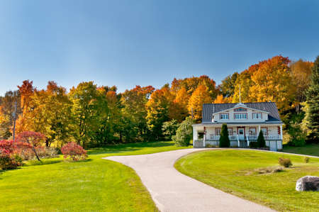 House in front of a autumn forest on a sunny day Editorial