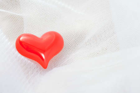 Red heart on a white veil for all kind of romantic occasions photo