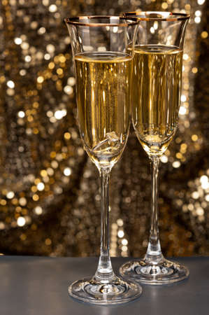silver flute: Champagne glasses with submerged ring in front of gold glitter background