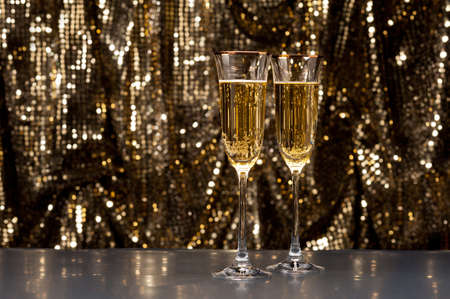 Champagne glasses in front of gold glitter background photo