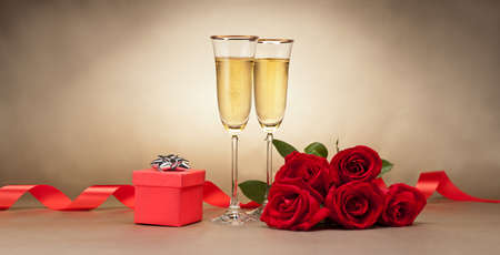 silver flute: Champagne glasses, present and roses in front of beige background Stock Photo