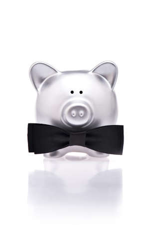 Silver piggy bank with bow tie over white photo